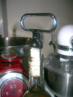 A two pronged cork extractor stuck in the top of a bottle