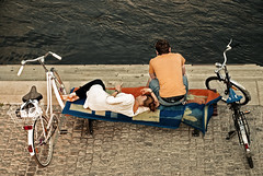 A Couple Framed By Bikes (rasenkantenstein) Tags: boy people woman man water girl bike june stairs river germany bench reading book spring couple stair steps bikes tshirt read step magdeburg blanket cloth elbe sachsenanhalt thepowerofnow