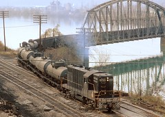Pittsburgh and Lake Erie local freight, powered by 1500 hp EMD GP-7 5733, leaving Neville Island, and entering McKees Rocks, PA, after crossing the back channel of the Ohio River, October, 1971 (Ivan S. Abrams) Tags: nyc arizona electric gm pittsburgh pennsylvania ivan detroit bridges trains getty bo freighttrains abrams railways freight locomotives londonontario gettyimages railroads csx generalmotors geep smrgsbord ambridge tucsonarizona pittsburghpa emd baltimoreandohio mckeesrocks nevilleisland ple chessiesystem alleghenycounty steelindustry dravo gp7 railfans 12608 electromotive dieselelectriclocomotive lagrangeillinois electromotivedivision trussbridges onlythebestare pittsburghandlakeerie gp7diesel ivansabrams trainplanepro pimacountyarizona safyan arizonabar arizonaphotographers ivanabrams newyorkcentralsystem cochisecountyarizona tucson3985 gettyimagesandtheflickrcollection electromotivediesel railbuffs copyrightivansabramsallrightsreservedunauthorizeduseofthisimageisprohibited tucson3985gmailcom ivansafyanabrams arizonalawyers statebarofarizona californialawyers generalmotorsdiesel copyrightivansafyanabrams2009allrightsreservedunauthorizeduseprohibitedbylawpropertyofivansafyanabrams unauthorizeduseconstitutestheft thisphotographwasmadebyivansafyanabramswhoretainsallrightstheretoc2009ivansafyanabrams abramsandmcdanielinternationallawandeconomicdiplomacy ivansabramsarizonaattorney ivansabramsbauniversityofpittsburghjduniversityofpittsburghllmuniversityofarizonainternationallawyer