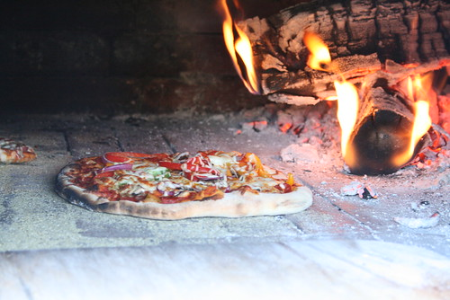 A pizza bakes inside the Mile End Bread Oven. Volunteers with the bread oven say they want to preserve traditional ways of preparing food. Just a few blocks away, the famed St-Viateur Bagel shop still uses a wood-fire oven.