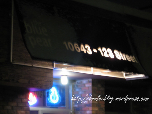 Exterior of The Blue Pear, with snow covering the name and a fuzzy shot of the neon pear above the door.