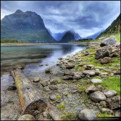 Milford Sound, Fiordland National Park, New Zealand :: HDR :: Vertorama (:: Artie | Photography ::) Tags: new christchurch mountain lake reflection nature photoshop canon landscape landscapes log rocks cs2 cloudy tripod wideangle zealand southisland milford 1020mm milfordsound hdr artie fiordland fiordlandnationalpark 3xp sigmalens photomatix tonemapping tonemap 400d rebelxti vertorama