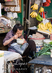 Chinese Woman Eating Lunch Outdoors (Jim Lopes Photography) Tags: china old people food woman shop fruit shopping lunch outdoors person hongkong store sitting break rice market eating chinese culture bowl bananas busy elderly chopsticks resting brunette kowloon clutter shopkeeper