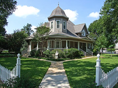 Grand Entrance (Texas Finn) Tags: windows white house beautiful grass statue fence texas landscaping lace queenanne steps lawn victorian front historic spire explore sidewalk oldhouse porch curtains whitepicketfence twostory frontporch turret picket weatherford wraparound
