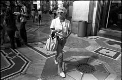 White Sunglasses - Milano (Dr Karanka) Tags: street blackandwhite italy milan film milano ilfordhp5 rodinal retrostyle 28mmlens asahipentaxsp2 deadcentrecomposition olderladywithwhitesunglasses insidelagalleria womanwithhandbag fds24hdrkaranka sttdebw