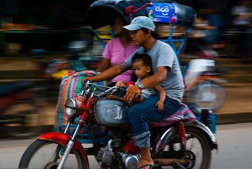 Family moving house on an auto-rickshaw in Luang Prabang, Laos