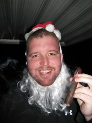 Travis is smoking a CAO America with a Santa hat and beard in order to win a cigar sampler from CAO. Travis won!
