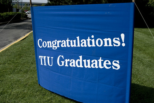 A sign in from of campus that states, Congratulations TIU Graduates!