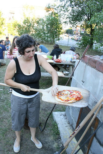 A volunteer checks a pizza before serving it to the hungry crowd at a public dinner last Saturday.