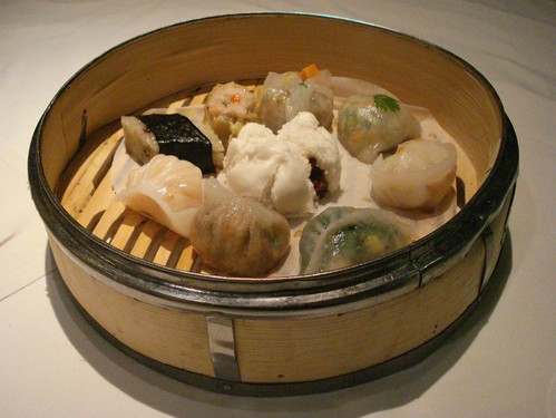 A wide circular bamboo steamer containing nine pieces of steamed dim sum, including a char siu bao sitting in the middle.