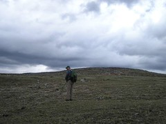 "Jim crossing the vast expanse of the ""tundra"" between the American and Canadian summits of Armstrong"