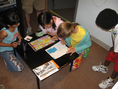 The kids pore over a copy of the CKUW Program Guide during a morning scavenger hunt.
