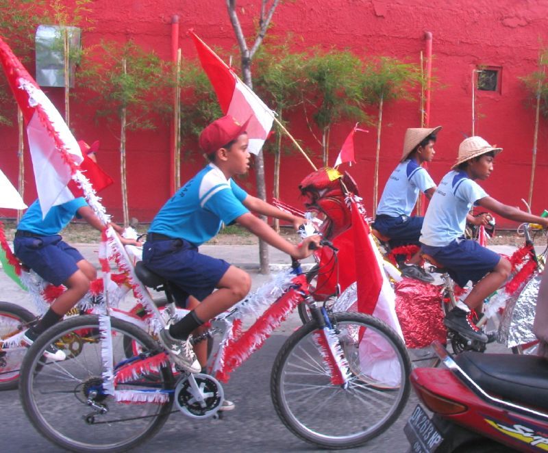 Schoolchildren riding bicycles in colours of Indonesian flag