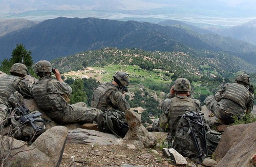 soldiers in afghanistan on a ridge surveying the terrian below
