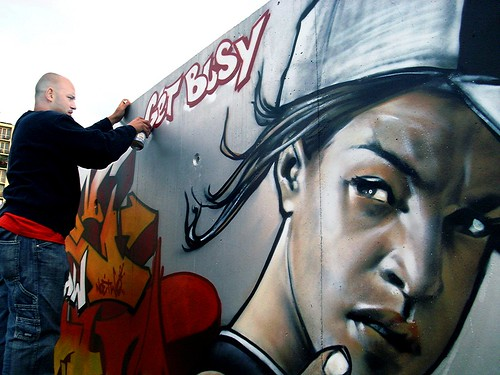 Paris artist applies final touches to a street mural.