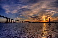 Sunset, Coronado Bridge, San Diego (Thad Roan - Bridgepix) Tags: california bridge blue light sunset sky orange sun sunlight reflection water silhouette yellow clouds sailboat skyscape landscape boat photo sailing shadows sandiego gray bridges wikipedia coronado span hdr bridging photomatix catamarran 200612 skyarchitecture bridgepixing bridgepix abigfave anawesomeshot amazingshots frhwofavs