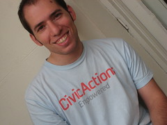 Photo of Gregory Heller smiling in a CivicActions Empowered T-shirt