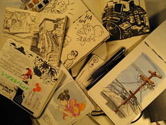 Moleskine Addiction - Exploded (artandstory) Tags: stilllife art moleskine pencil ink watercolor artwork mess g4 open display desk stickers cartoon journal sketchbook stack smoking collection scatter doodle pile geisha telephonepole addiction planner brushpen sketchcrawl exploded splayed waterbrush