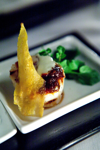 Grilled scallop with sweet chili sauce, crème fraiche and green plantain crisp
