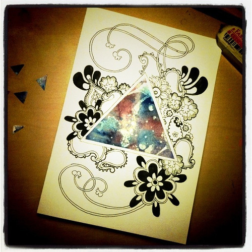 Photo of a card with a triangle cut out of watercolour with splatters of blue, red and white paint surrounded by paisley doodling.