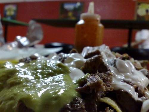 Super Nachos with the Orange Sauce looming behind