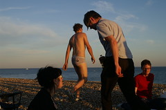 Off for a swim (A Silent Republic) Tags: sunset sea people man english beach swim sussex brighton picnic pants july going 2006 pebbles east barbeque channel