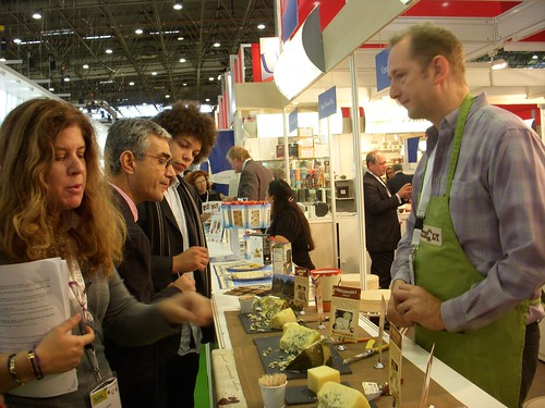Trade visitors sample a variety of cheeses at the Rogue Creamery stand in the USA Pavilion. Rogue Creamery, an artisan cheese company, is dedicated to sustainability and the art and tradition of making the world's finest handmade cheese.
