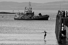 The Bait Boy (Pensiero) Tags: boy people blackandwhite water scotland boat dock dive oban scozia exb titoloautotitolante