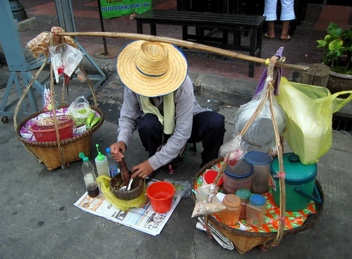 Street vendor making green banana salad