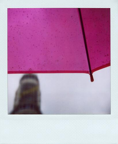 Fotografía de un paraguas rosa en un día de lluvia en la Gran Vía madrileña con el clásico edificio del anuncio de Scheweppes al fondo