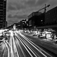 city lights (Georgios Karamanis) Tags: street sky bw cars night clouds buildings lights nightshot sweden stockholm crane trails sverige bwdreams explored karamanis