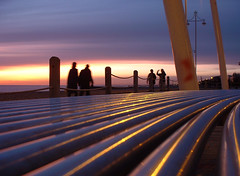 Sunset Curve (Dominic's pics) Tags: pink sunset sky orange bench brighton streetlamps steel lilac promenade reflective lit seafront curved walkers stainless polished clouded childrensplayground ropebarrier