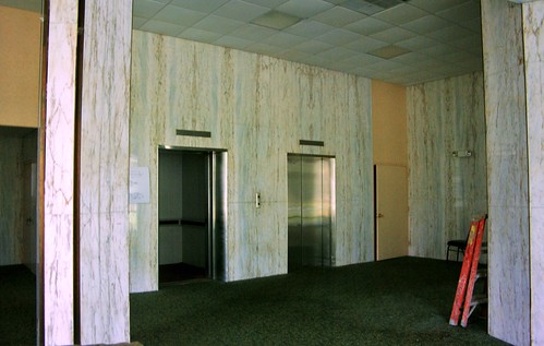 Tower lobby elevators with marble wall and drop ceiling