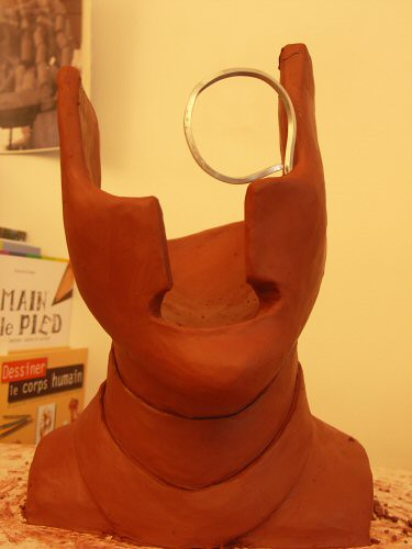 Sculpture en terre surréaliste vue de face représentant un visage de gardien figuré par un masque de samouraï creux avec un monocle – Sandrine Vallée