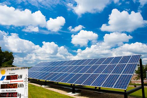 A solar array under a mostly sunny sky