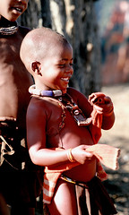 Himba child smiling - Namibia (Christophe Paquignon) Tags: world pictures voyage africa trip travel portrait color travelling colors smile face smiling canon children photography eos photo gesicht foto tour child faces image photos pics couleurs african picture culture images tribal du adventure safari round afrika around tribe christophe monde ethnic backpacker amateur pict namibia autour couleur tribo indigenous visage himba afrique ethnology tribu aroundtheworld aventure namibie visages tourdumonde 50d tribus ethnie 400d himbas eos400d kryyslee christophepaquignon paquignon