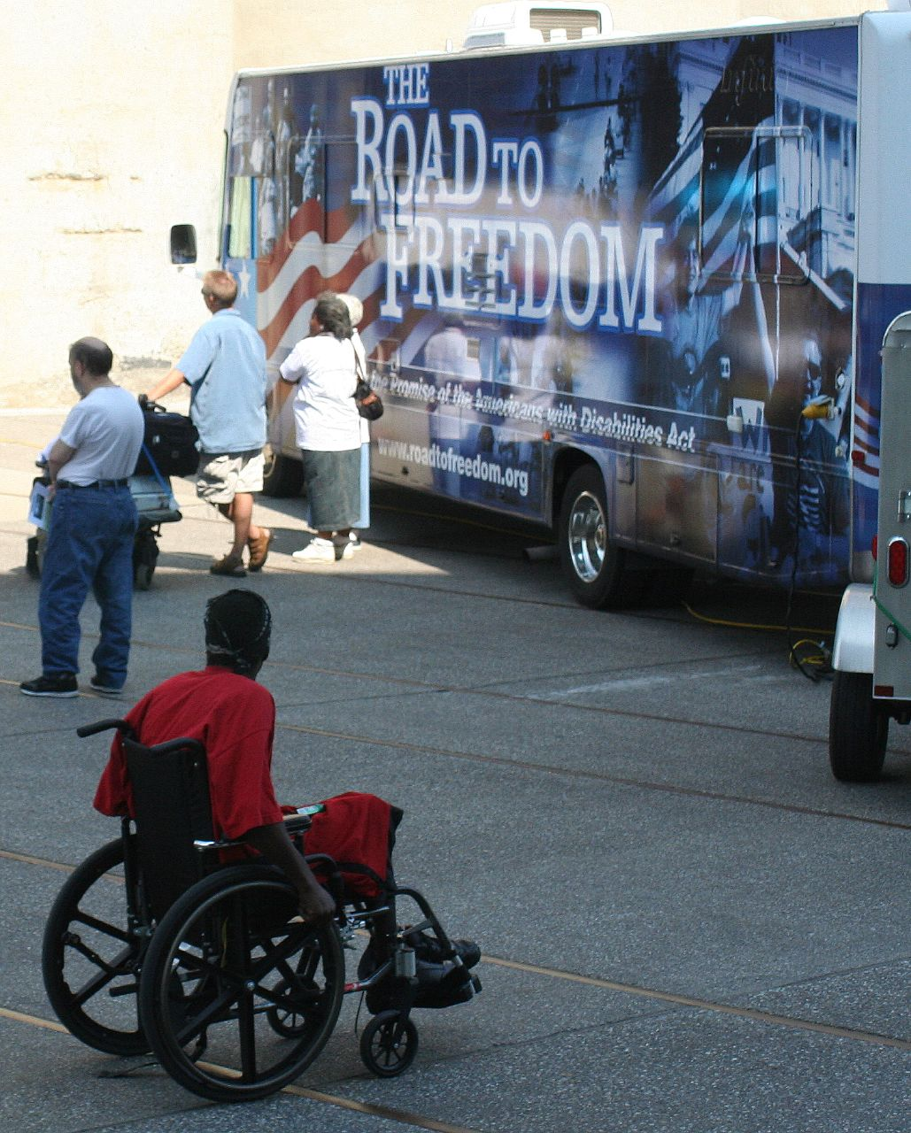 Photo from Minneapolis Road to Freedom tour, with a person in a wheelchair approaching the Road to Freedom van, decorated with images from disability rights work