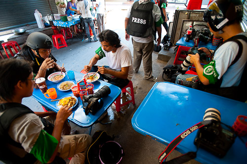 Photojournalists eating lunch at a noodle stall near Thanon Silom, Bangkok