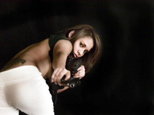 Girl with a gun doing a Bond Girl act