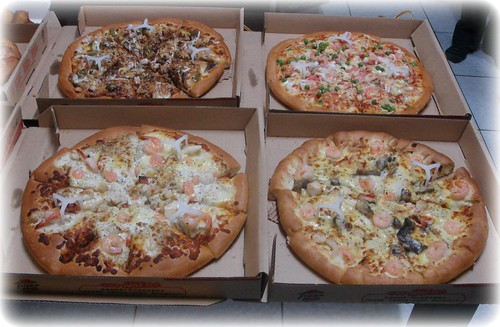 three different kinds of seafood pizza and one black pepper beef pizza