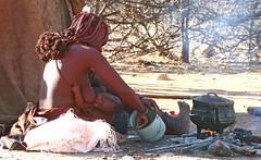 Himba mother eating and feeding her baby - Namibia (kryyslee) Tags: world pictures voyage africa trip travel people baby color travelling colors canon photography eos photo foto tour image photos pics couleurs african mother picture culture images tribal du adventure safari mum round afrika around feed tribe christophe monde ethnic backpacker amateur pict namibia autour couleur tribo indigenous himba afrique ethnology tribu aroundtheworld aventure namibie tourdumonde 50d tribus ethnie 400d eos400d kryyslee christophepaquignon paquignon