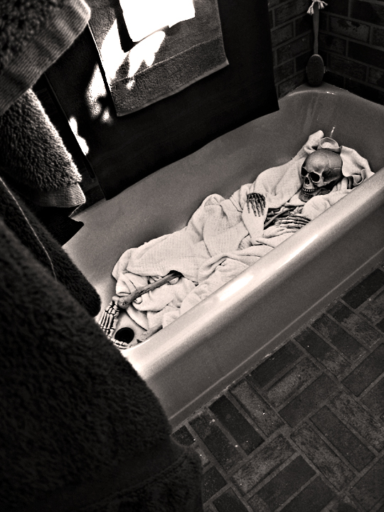 skeleton wrapped in a blanket in the tub+black and white