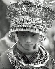 a girl in a polo-neck (richard thomson) Tags: china portrait blackandwhite bw topf25 festival 35mmfilm guizhou miao headdress nikonfe2 minorities kaili miaofestival