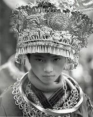 a girl in a polo-neck (richard thomson) Tags: china portrait blackandwhite bw topf25 festival 35mmfilm guizhou miao headdress nikonfe2 minorities kaili miaofestival