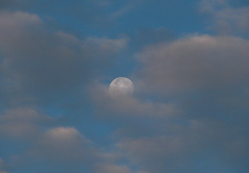 Daylight Moon hiding behind clouds