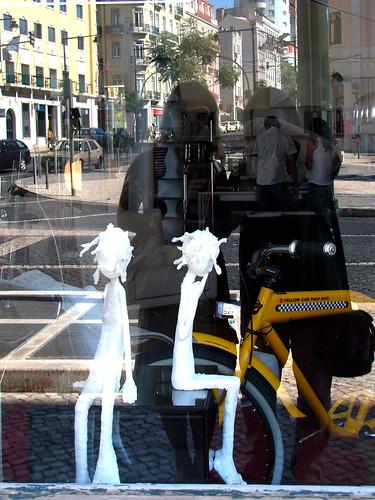 Lisboa reflectida entre estátuas de gesso e bicicletas amarelas....