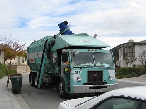 垃圾車的機械手臂把垃圾桶往車艙倒