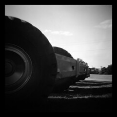 Big Wheel (Ralph Krawczyk Jr) Tags: light shadow summer sky blackandwhite bw grass wheel metal dark giant outside toycamera lofi ground plastic equipment machinery powerlines diana massive diafine softfocus rim 248 lateafternoon vingette heavyduty earthmovers gianormous aristaeduultra100 120mediumformat ralphkrawczykjr wixommichigan