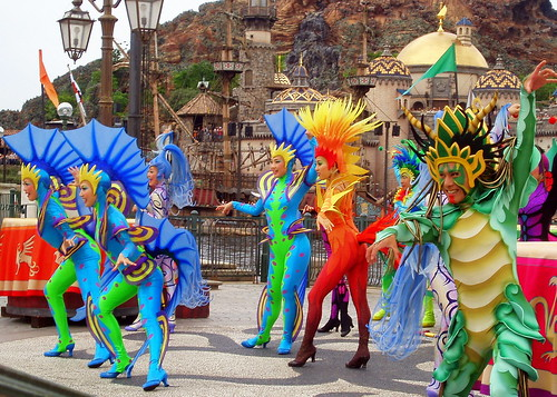 In select areas on shore, colorful dancers create a bright and high energy atmosphere as they swirl around with drums and staffs.