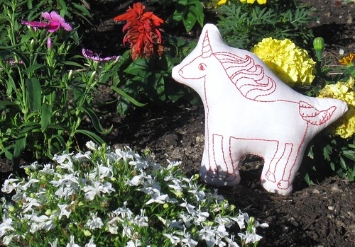 Unicorn frolics in the flower beds.